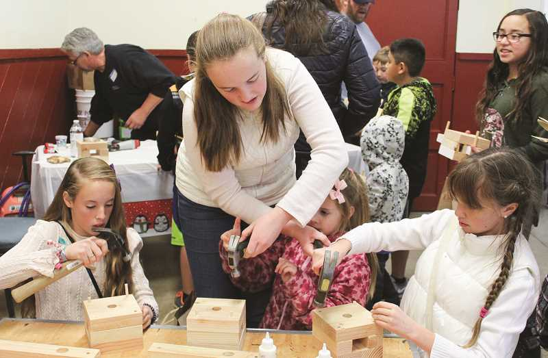 CENTRAL OREGONIAN FILE PHOTO  - Children get some help on the wood project during Santa's Workshop last year. The annual Crook County Parks and Rec event is set for this Saturday at Carey Foster Hall.