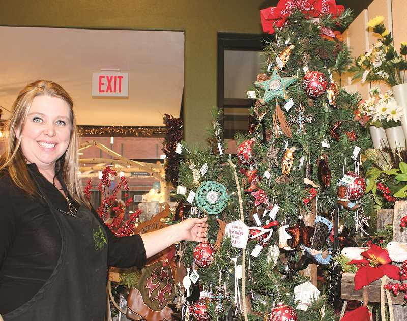 HOLLY SCHOLZ/CENTRAL OREGONIAN  - The Posie Shoppe owner Michelle Simpson, who has helped organize the annual Holiday Open House and Ladies Night, puts the finishing touches on a Christmas display at her shop. The annual event is planned for 5 to 8 p.m. Thursday, Nov. 15 at 10 downtown businesses.