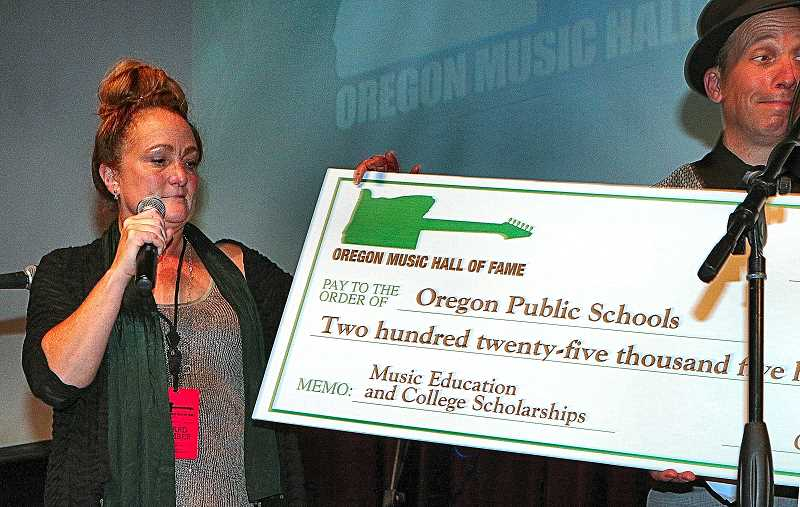 DAVID F. ASHTON - Presenting the giant check, showing how much OMHOF raised to help support music organizations, is their organizations Co-Founder, and Director of Scholarships and Music Education, Janeen Rundle.
