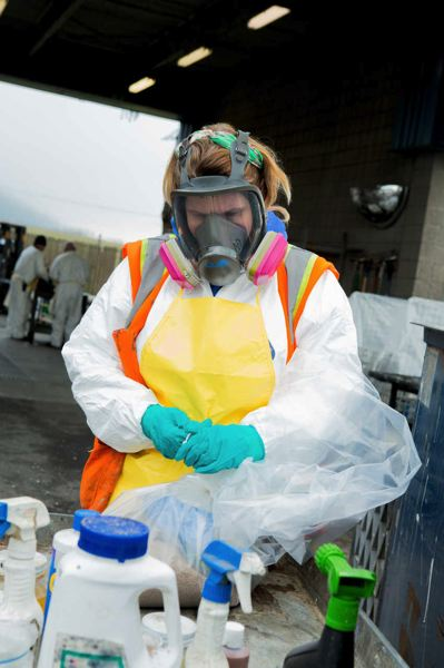 COURTESY METRO  - A worker carefully handles hazardous waste brought by a member of the public to a Metro facility in Oregon City.