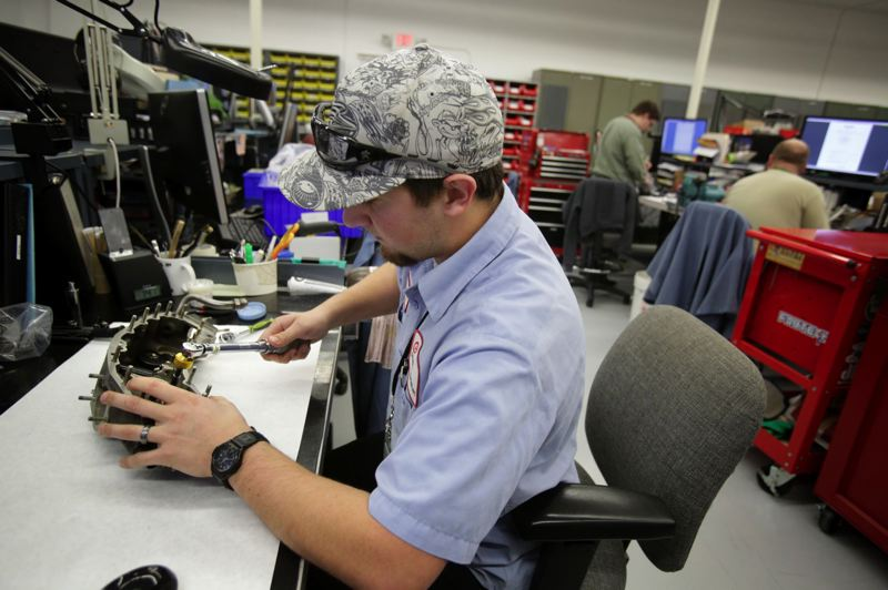 PAMPLIN MEDIA GROUP: FILE PHOTO - Kenny Cooper fixes up an accessory drive gear box at Columbia Helicopters.