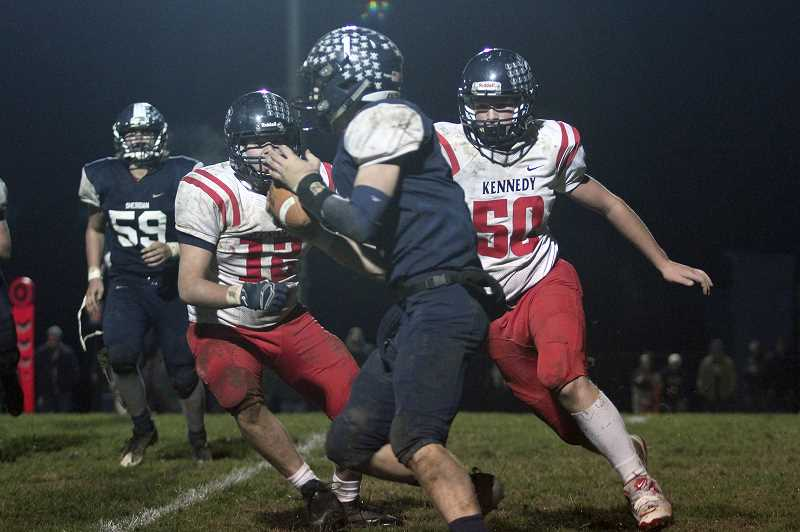 PHIL HAWKINS - Kennedy's Brady Traeger (left) and Cole Boen converge on Sheridan quarterback Jacob DeBoff in the Trojans' win over Sheridan. Kennedy held the No. 2 Spartans to less than 100 yards of offense in the win.
