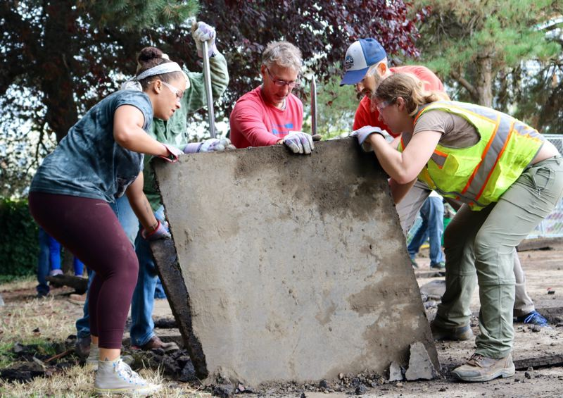 PAMPLIN MEDIA GROUP FILE PHOTO - Volunteers pry up a chunk of the Boise-Eliot/Humboldt Elementary schoolyard on Saturday, Sept. 22 in Portland. A new national report says Oregon is No. 3 for the percentage of volunteers.