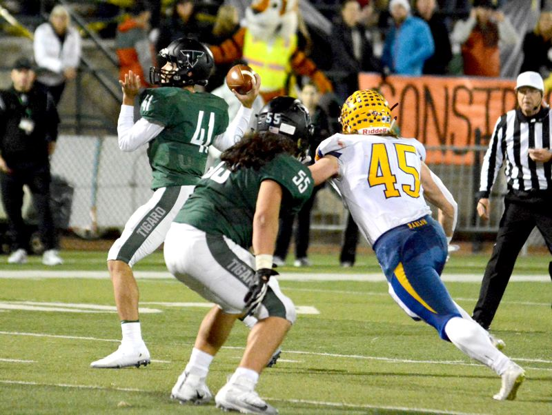 PMG PHOTO: DAVID BALL - Tigard sophomore quarterback Drew Carter (41) looks to throw a pass behind a block by senior Isaia Porter during Fridays win over Barlow.
