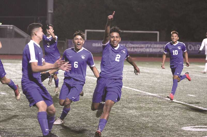 PHIL HAWKINS - Woodburn sophomore Jimmy Martin celebrates with his teammates after scoring the Bulldogs' first goal of the night against North Marion, four minutes into the game.