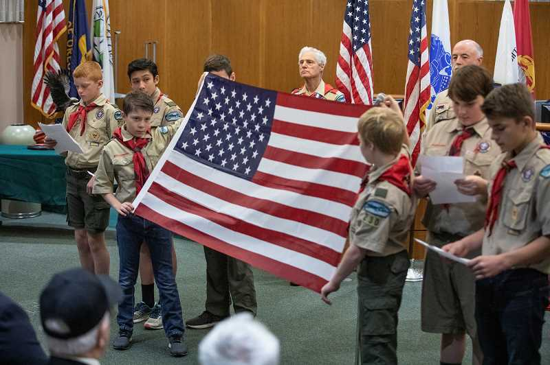 REVIEW PHOTO: JONATHAN HOUSE - Lake Oswego Boy Scout Troop 230 unfurls the American Flag during the Veterans Day program at City Hall.