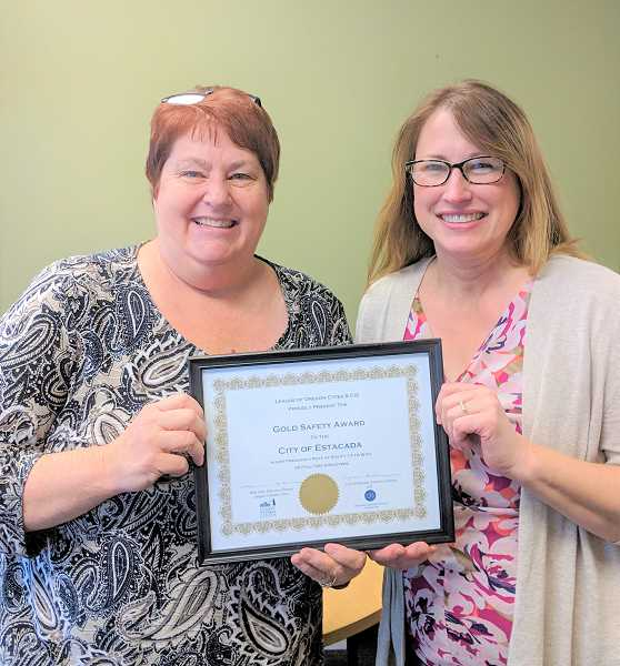ESTACADA NEWS PHOTO: EMILY LINDSTRAND - City Manager Denise Carey and Assistant to the City Manager Melanie Wagner show of the citys gold medal for safety award from Citycounty Insurance Services.