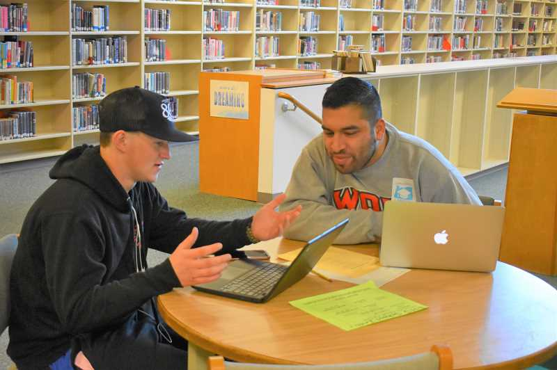 ESTACADA NEWS PHOTO: EMILY LINDSTRAND - An Estacada High School senior works with alum Ivan Acosta during the schools College Application Week. The program gave students time to apply to colleges and for financial aid.