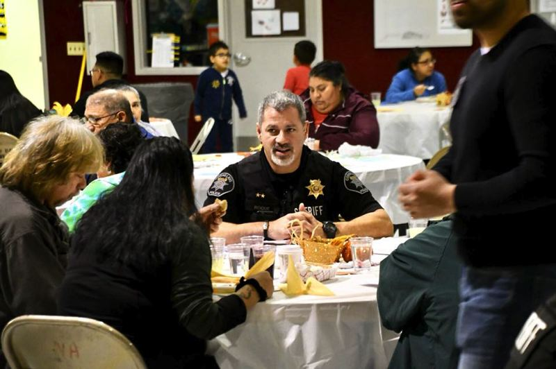 COURTESY PHOTO: WASHINGTON COUNTY SHERIFF'S OFFICE - Cornelius Police Chief Al Roque visits with guests at last year's community Thanksgiving dinner in Cornelius.