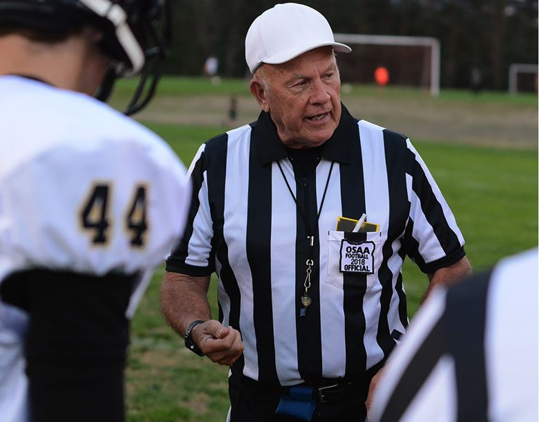 OUTLOOK PHOTO: DAVID BALL - John Birkhofer conducts a the coin flip before an early-season game in Corbett. He has been calling prep football and basketball games for more than 40 years.