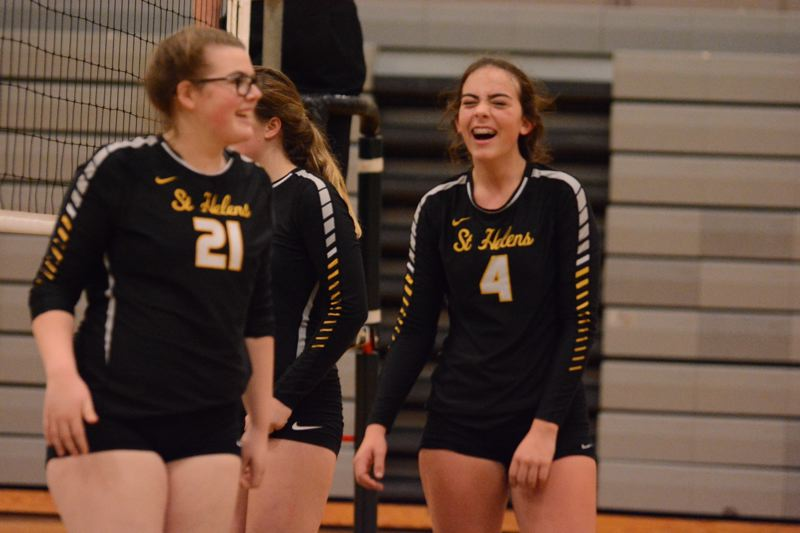 PAMPLIN MEDIA GROUP PHOTO: JIM BESEDA - Karlee Webster (right) and fellow St. Helens Lion Brynn Austin enjoy the outcome of a point during the 2018 volleyball season.