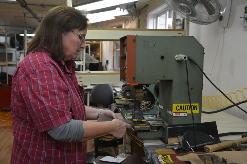 SPOTLIGHT PHOTO: COURTNEY VAUGHN - Pat Barnard of St. Helens embosses the Wesco logo onto leather cut-outs in the Scappoose factory. The leather pieces will soon be attached to soles and molded to the shape of a boot.