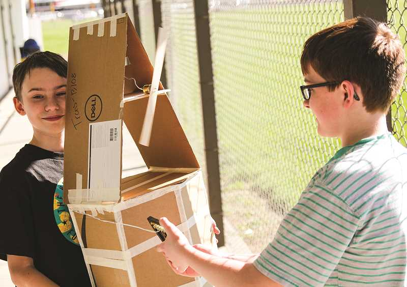 PHOTO COURTESY OF JIM CROUCH  - Dylan James, left, and Kellen Grist show their solar-powered windmill they made in their seventh-grade engineering class.