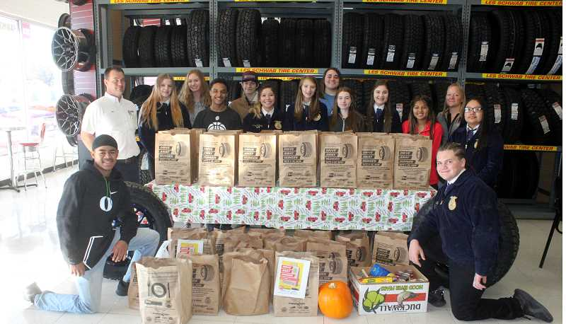 SUSAN MATHENY/MADRAS PIONEER - Les Schwab Manager Ron Hollingshead, back left, stands with members of the Madras FFA, who arrived to take food donations to a Madras food pantry.