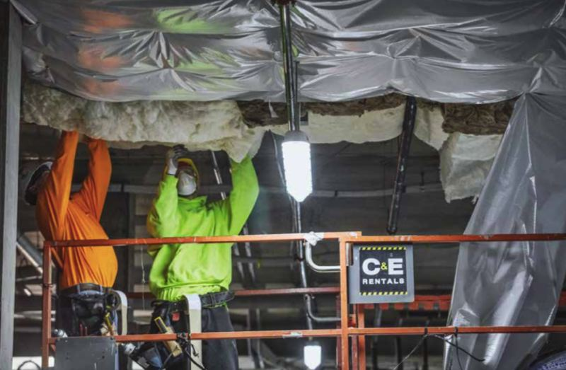PAMPLIN MEDIA GROUP: JONATHAN HOUSE  - Workers finish the insulation at the Broadstone Reveal apartments in the Pearl District. The project superintendent has to coordinate dozens of subs who come back to finish missing and damaged work before the building is ready for occupancy.