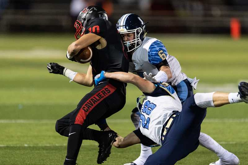 STAFF PHOTO: CHRISTOPHER OERTELL - Liberty's Nik Reitzug (6) and AJ Records (28) try and tackle Clackamas' Anthony Talavera during the Falcons' game against the Cavaliers, Nov. 16, at Clackamas High School.