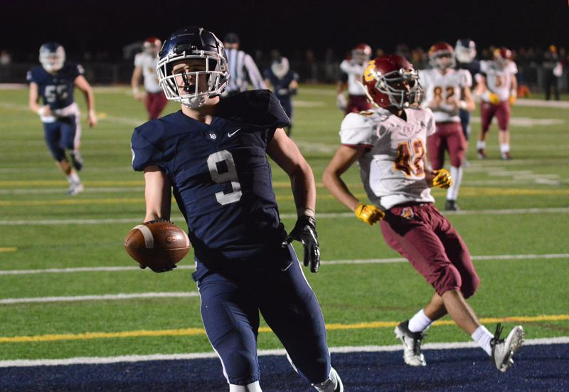 PAMPLIN MEDIA: DAVID BALL - Lake Oswegos Casey Filkins tosses the ball to the official after scoring on a 19-yard fourth-down touchdown catch to seal Fridays quarterfinal win.