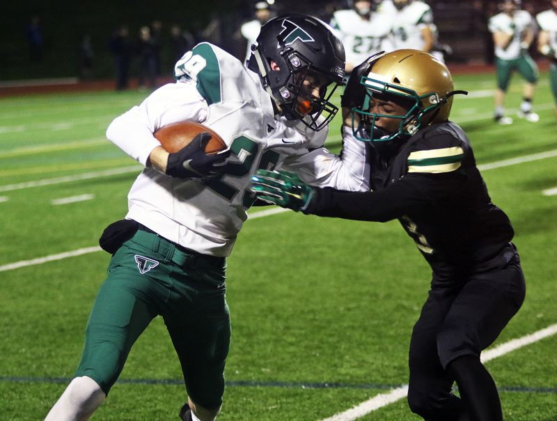 TIMES PHOTO: DAN BROOD - Tigard senior receiver Luke Ness (left) looks to get past Jesuit senior Gary Hollands during Friday's state playoff quarterfinal game.