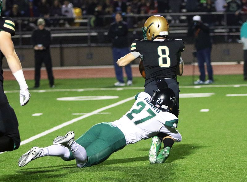TIMES PHOTO: DAN BROOD - Tigard senior Fletcher Ahl drags down Jesuit quarterback Will Spitznagel for a sack during the first quarter of Friday's game at Jesuit.