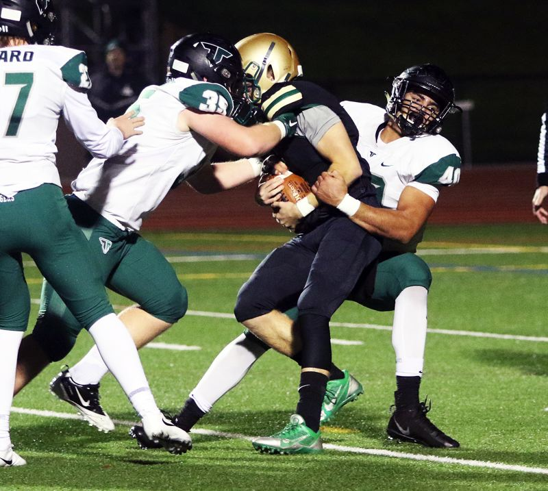 TIMES PHOTO: DAN BROOD - Tigard seniors Noah Jackman (right) and Carter Dennis team up to sack Jesuit senior quarterback Will Spitznagel.