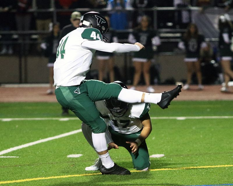 TIMES PHOTO: DAN BROOD - Tigard junior Jackson Cleaver, with senior Carson Crist holding, kicked a 23-yard field goal during Friday's game at Jesuit.