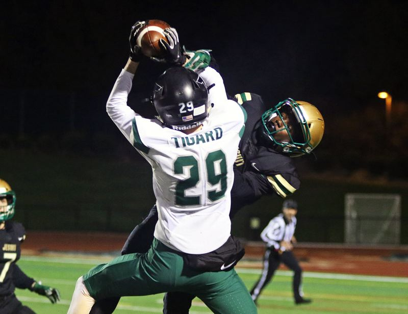 TIMES PHOTO: DAN BROOD - Tigard senior Luke Ness (29) reaches up to make a catch against Jesuit senior Gary Hollands during Friday's game.