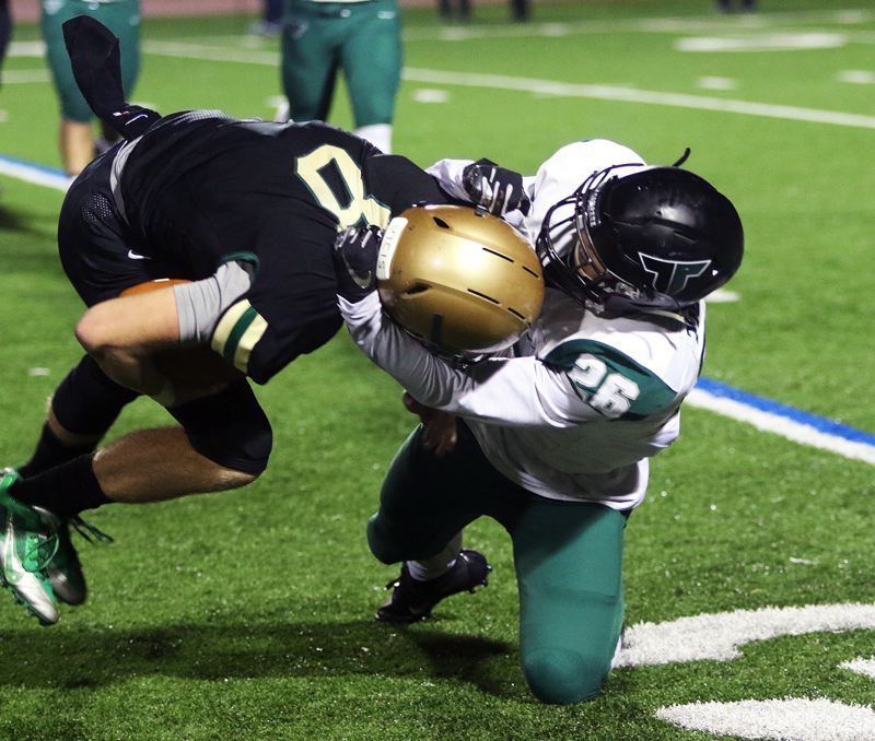 TIMES PHOTO: DAN BROOD - Tigard senior Jazz Ross (right) drags down Jesuit senior Will Spitznagel for a quarterback sack during Friday's state playoff quarterfinal game.
