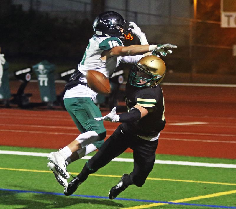 TIMES PHOTO: DAN BROOD - Tigard junior Max Lenzy (left) and Jesuit senior Colin McMahon battle for the ball in the end zone during Friday's state playoff quarterfinal game at Jesuit.