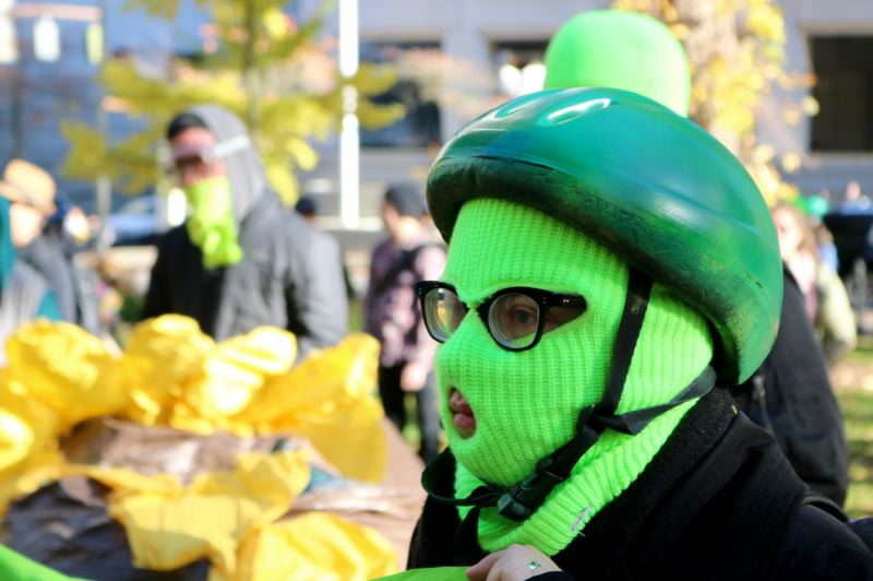 TRIBUNE PHOTO: ZANE SPARLING - An anti-fascist protesters wears a green mask and a helmet in Chapman Square Park on Saturday, Nov. 17 in Portland.