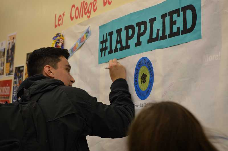 SPOKESMAN PHOTO: CLARA HOWELL  - Chris Grizzell signs the #IApllied poster after completing a college application.