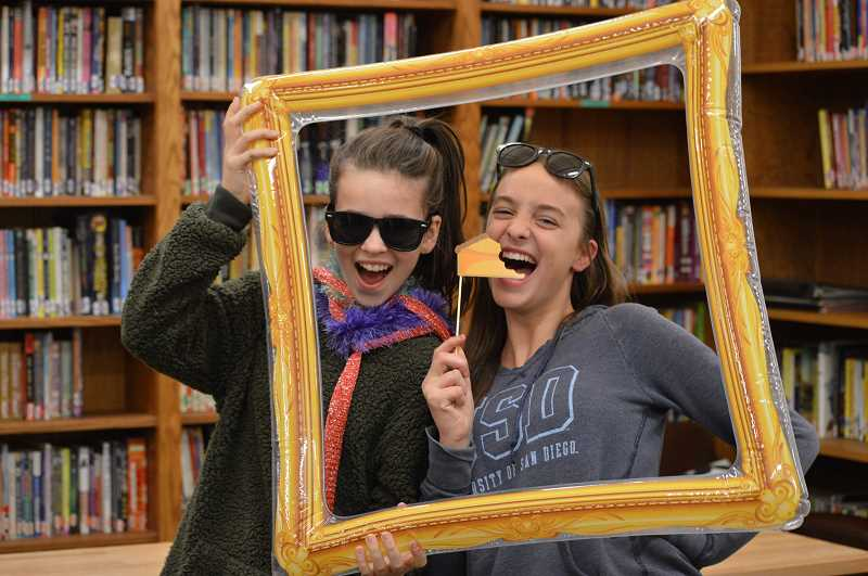 SPOKESMAN PHOTO: CLARA HOWELL  - Sixth-graders Emma Valerius, left, and Caroline Laidlow take pictures in the photo booth at Friendsgiving.