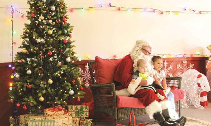 JASON CHANEY/CENTRAL OREGONIAN - Yohan, left, and Xitlali Robles sit on Santa's lap and pose a photo during the event.