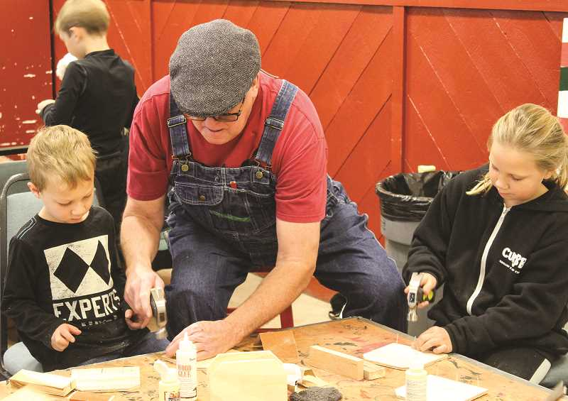JASON CHANEY/CENTRAL OREGONIAN - John Bond helps Trevor Bigby, left, and Leah Illingworth with the wooden napkin holder project.