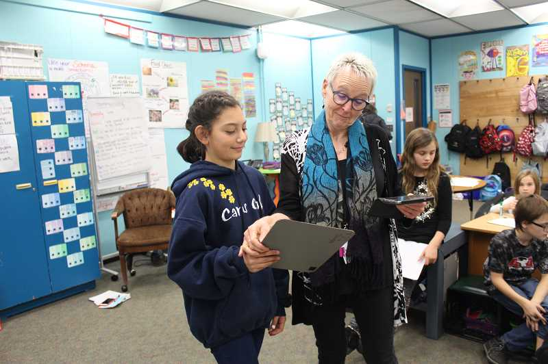 HERALD PHOTO: KRISTEN WOHLERS - Whyte helps fifth-grade student Carina Sanchez with writing lyrics.