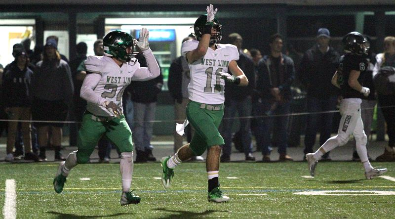 TIDINGS PHOTO: MILES VANCE - West Linn senior Brodie Corrigan (right) and teammate Cole Peters run off the field after Corrigan made an interception in the end zone against Sheldon on Friday night.