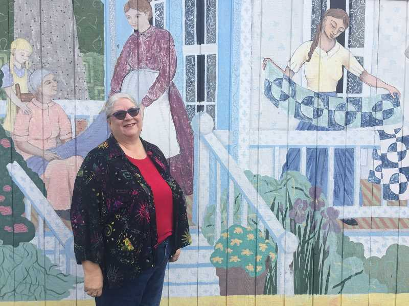 FILE PHOTO - Gloria Polzin beams in front Estacadas Quilt Club mural. After more than a decade of work on the Lucky Dawg World and eNews, Polzin has hung up her hat.