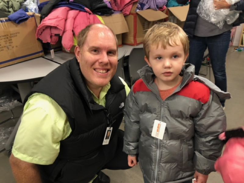 SUBMITTED PHOTO - Clackamas Sunrise Rotary member Ryan Hahn helps a young resident of the Clackamas Town Center Court Apartments pick out a new free coat courtesy of the clubs fundraising efforts.