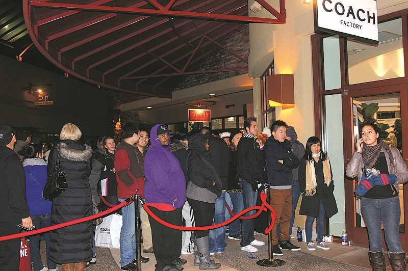 FILE PHOTO - Shoppers line up outside the Coach Factory store at Woodburn Premium Outlets. The mall of nearly 200 stores will open at 6 p.m. Thanksgiving Day and remain open through the night, a precursor to Black Friday.