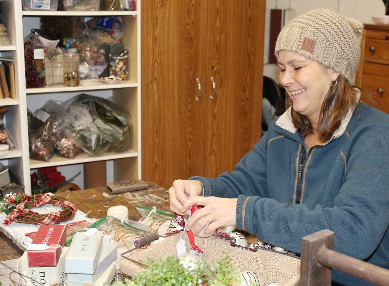 HOLLY M. GILL/MADRAS PIONEER - Julie Hartman works on labeling Christmas ornaments and wooden crafts in her workshop. Hartman and other local crafters are getting ready for holiday bazaars, boutiques and markets, which will be offered over the next few weeks before Christmas.