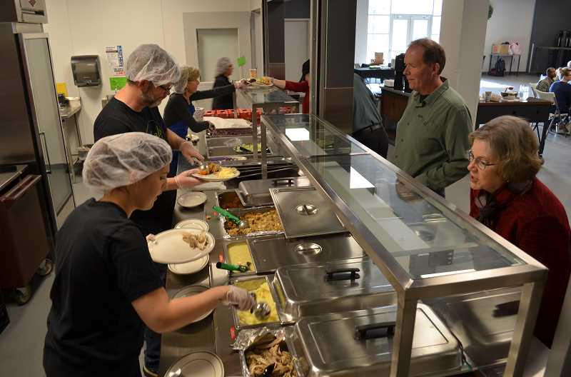STAFF PHOTO: GEOFF PURSINGER - Volunteers with Meals on Wheels serve a Thanksgiving meal during a holiday dinner on Thursday. Nov. 15. The organization recently moved to a new headquarters at Sonrise Church, near Orenco.