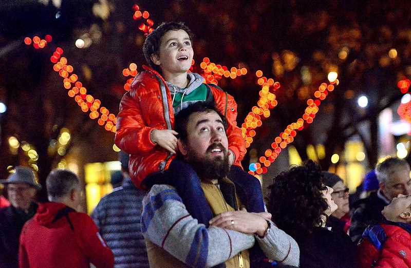 REVIEW PHOTO: VERN UYETAKE - Jack Barbee watches in wonder from dad Jason Barbee's shoulders during last year's holiday celebration in Millennium Plaza Park. Lake Oswego's 54th-annual event kicks off Friday at 5:30 p.m.