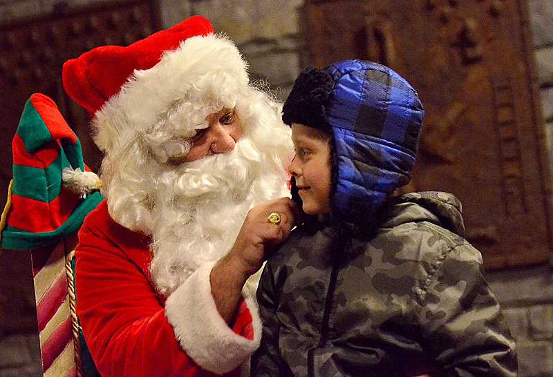 REVIEW PHOTO: VERN UYETAKE - Santa visits with Sullivan Fillmore during last year's holiday celebration in Millennium Plaza Park. The jolly ol' elf will make a return appaearance at this year's event on Friday.