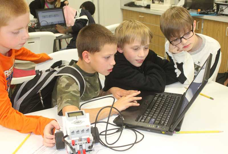 SUSAN MATHENY/MADRAS PIONEER - Learning center students Trenton Layton, left, Tobias May, Jaydin Hatch, and Camron Brierley look up ways to program their robot in the after-school Robotics class.