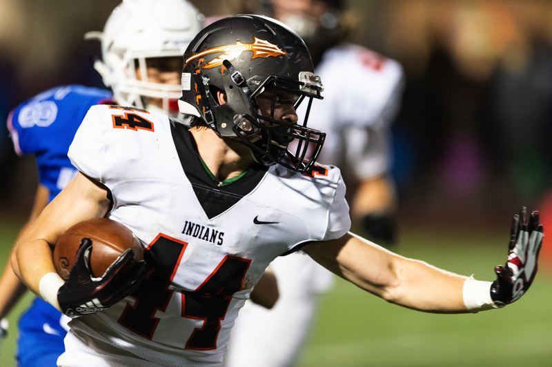PAMPLIN MEDIA GROUP PHOTO: CHRISTOPHER OERTELL - Connor McNabb of Scappoose High prepares to stiff-arm a defender. McNabb made the all-Northwest Oregon Conference team on offense, defense and special teams.