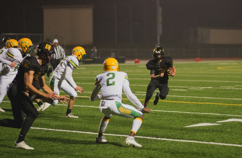 PHOTO COURTESY: JEREMY DUECK - Isaiah Bettencourt, a senior at St. Helens High, looks to beat Cleveland defenders on a kick return.