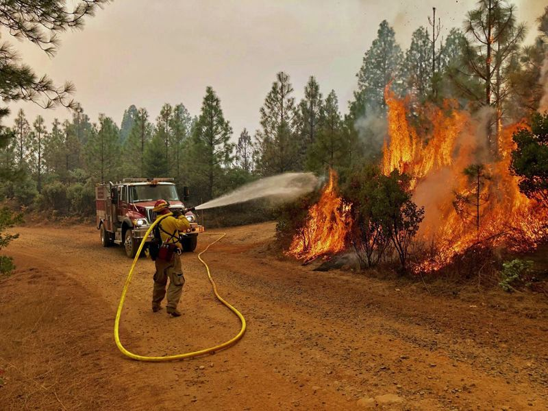 PHOTO: FIREFIGHTER BRYAN SIMMONS - A lone firefighter with a hose attempts to battle back a fire in California.