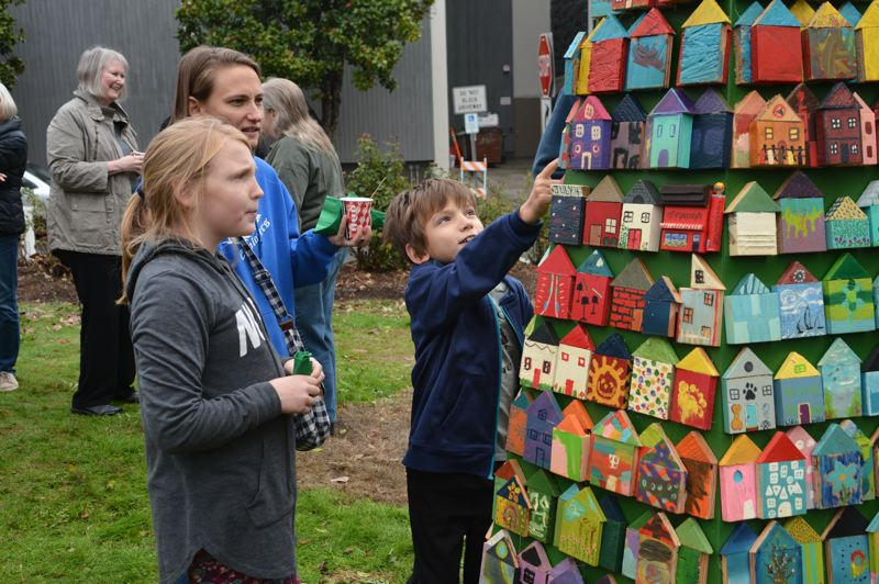 SPOTLIGHT PHOTO: COURTNEY VAUGHN - Jayden DeGroot points to a decorated house on display as part of a This Is Us St. Helens public art installation in the Columbia Courthouse Plaza. Behind him, Kayla and mom, Gina DeGroot, check out the painted houses.