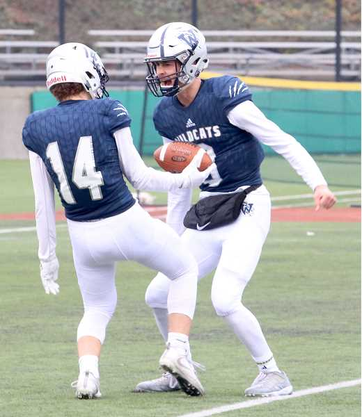 SPOKESMAN PHOTO: BRIAN MONIHAN - Wilsonville's Overholt celebrates with senior Grant Irby after his 25-yard touchdown reception over the middle. That pass gave Nathan Overholt the record for most passing touchdowns, surpassing Beaverton's Taylor Barton in 1999.