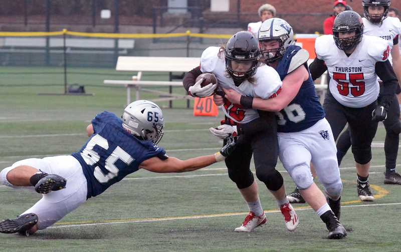 SPOKESMAN PHOTO: TANNER RUSS - Wilsonville seniors Caleb Baker and Kalei Kauhi take down a Thurston running back.