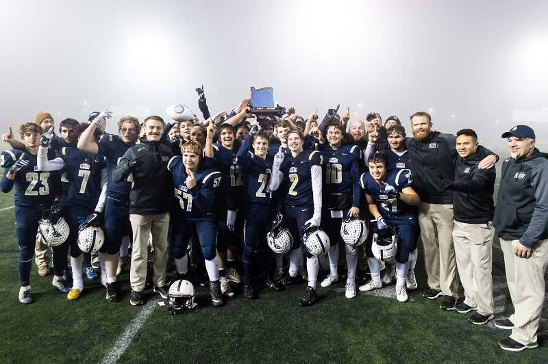 STAFF PHOTO: CHRISTOPHER OERTELL - Banks players and coaches pose for a photo with the state championship trophy after defeating Seaside, Nov. 24, at Hillsboro Stadium.